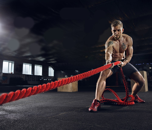 healthy man athelete with a training rope